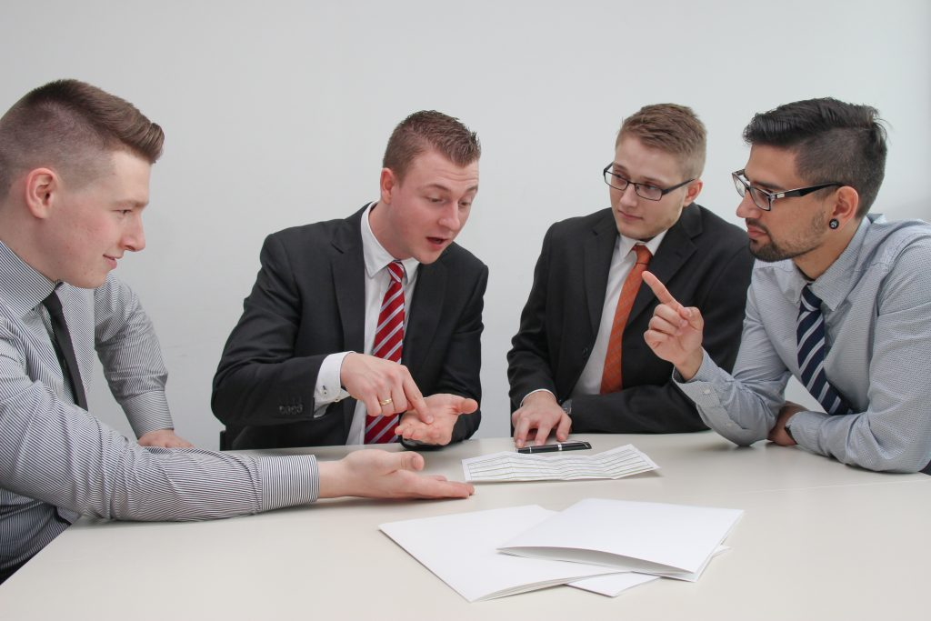 Four office workers having a discussion - Octopus Personnel how to reduce employee turnover