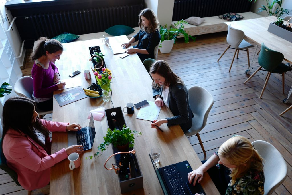 Women working at a large table in an office - Octopus Personnel how to reduce employee turnover