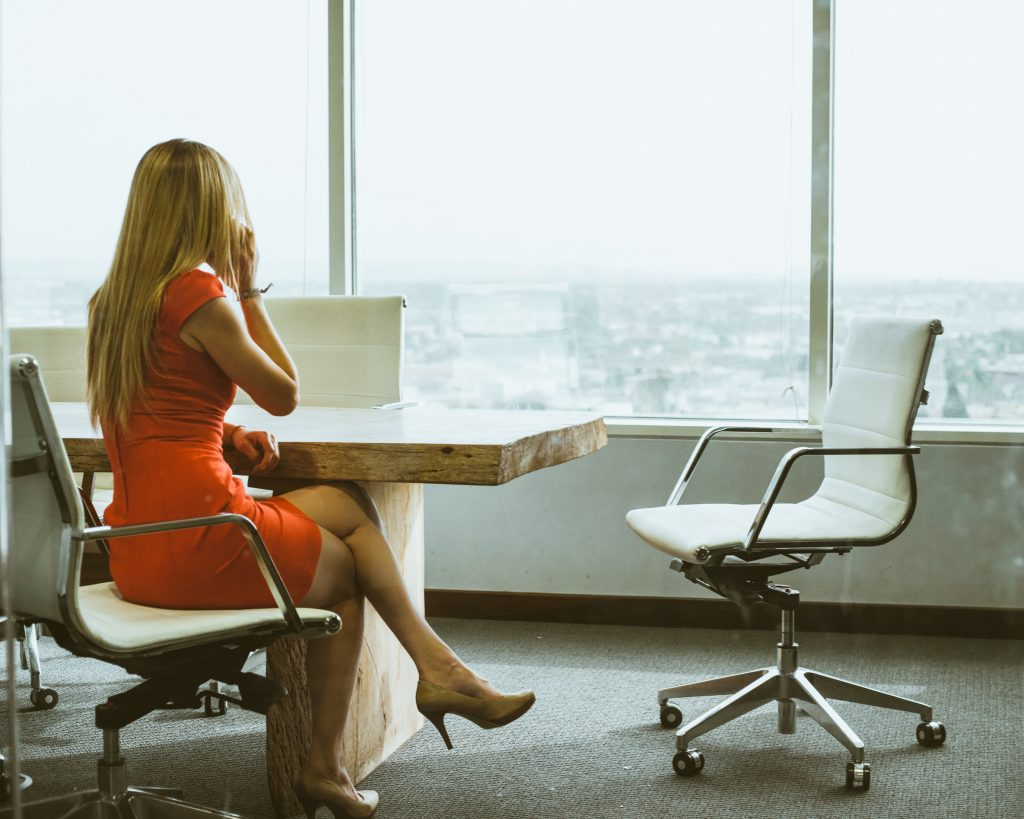 A woman sitting at a desk looking out of the window on a phone - Octopus Personnel how to reduce employee turnover