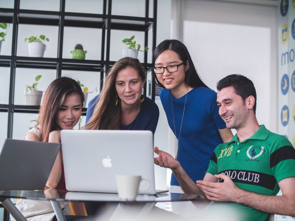 Four people collaborating around a laptop - Octopus Personnel Speak Out against Racism and Discrimination in the Workplace