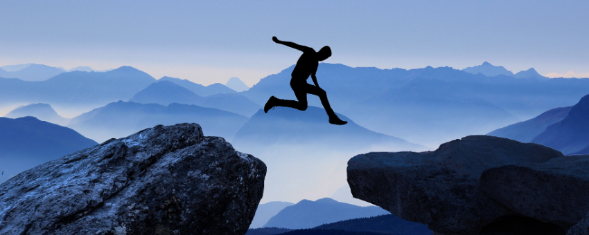 Man leaping between two high rocks - Describe a difficult work situation