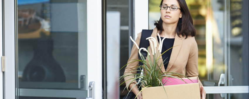 Woman leaving an office with belongings in a box: What to do when you've been made redundant